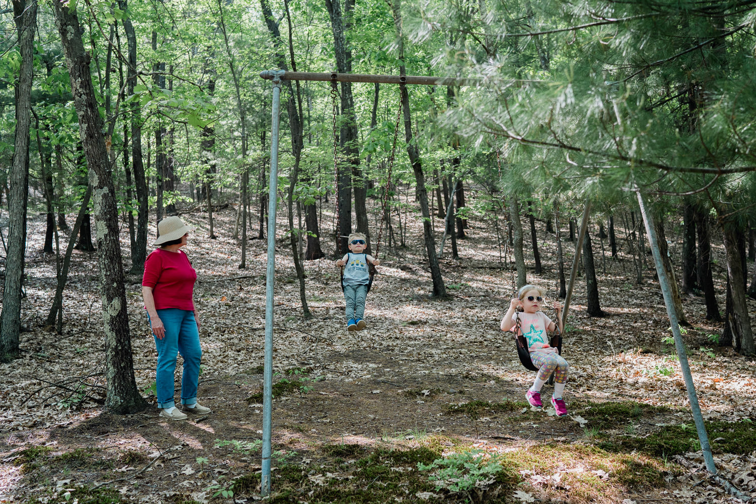 Children play on swings in the woods.
