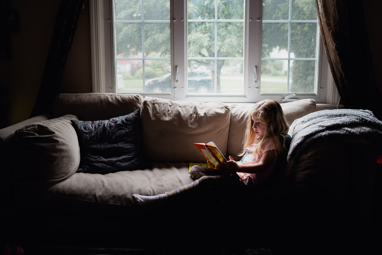 A little girl reads on a sofa.
