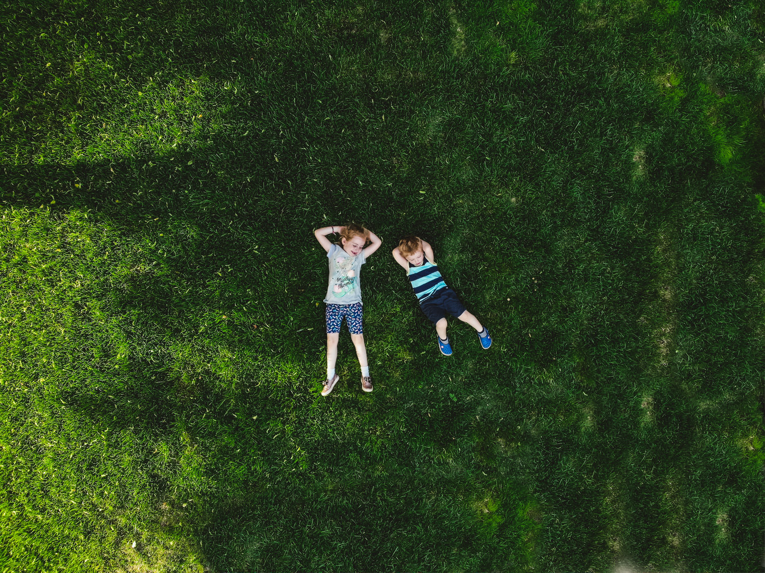An aerial shot of two children lying on the grass.