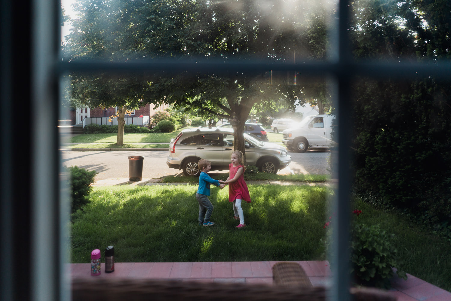 Two children play on a front lawn.