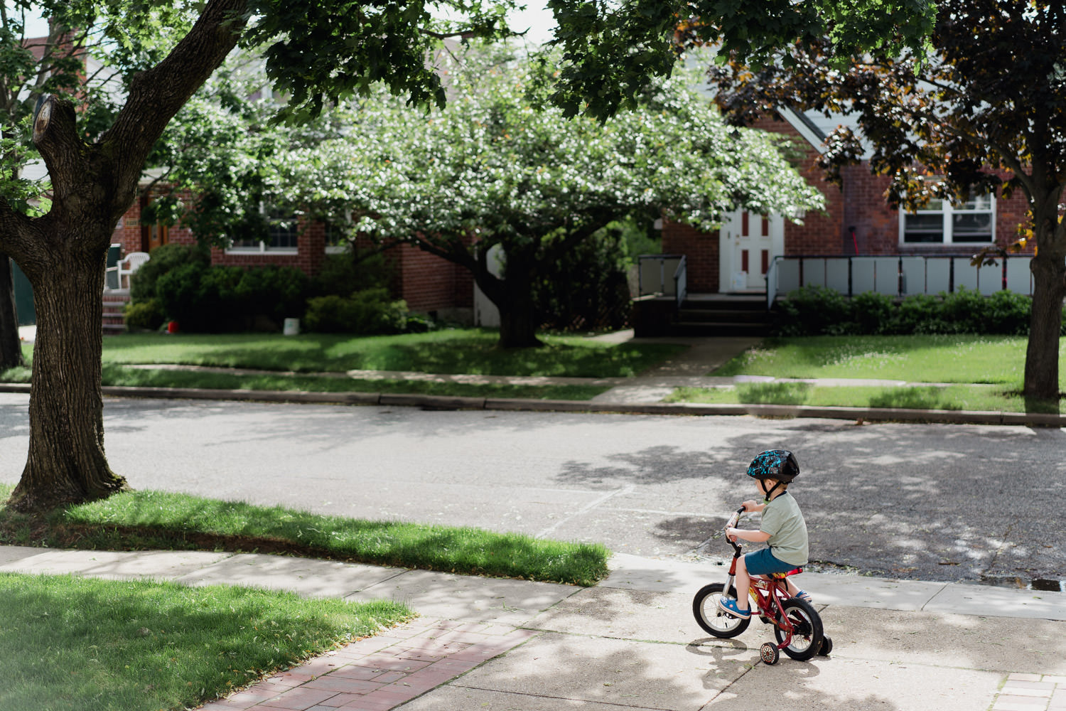A little boy rides his bike in a driveway.