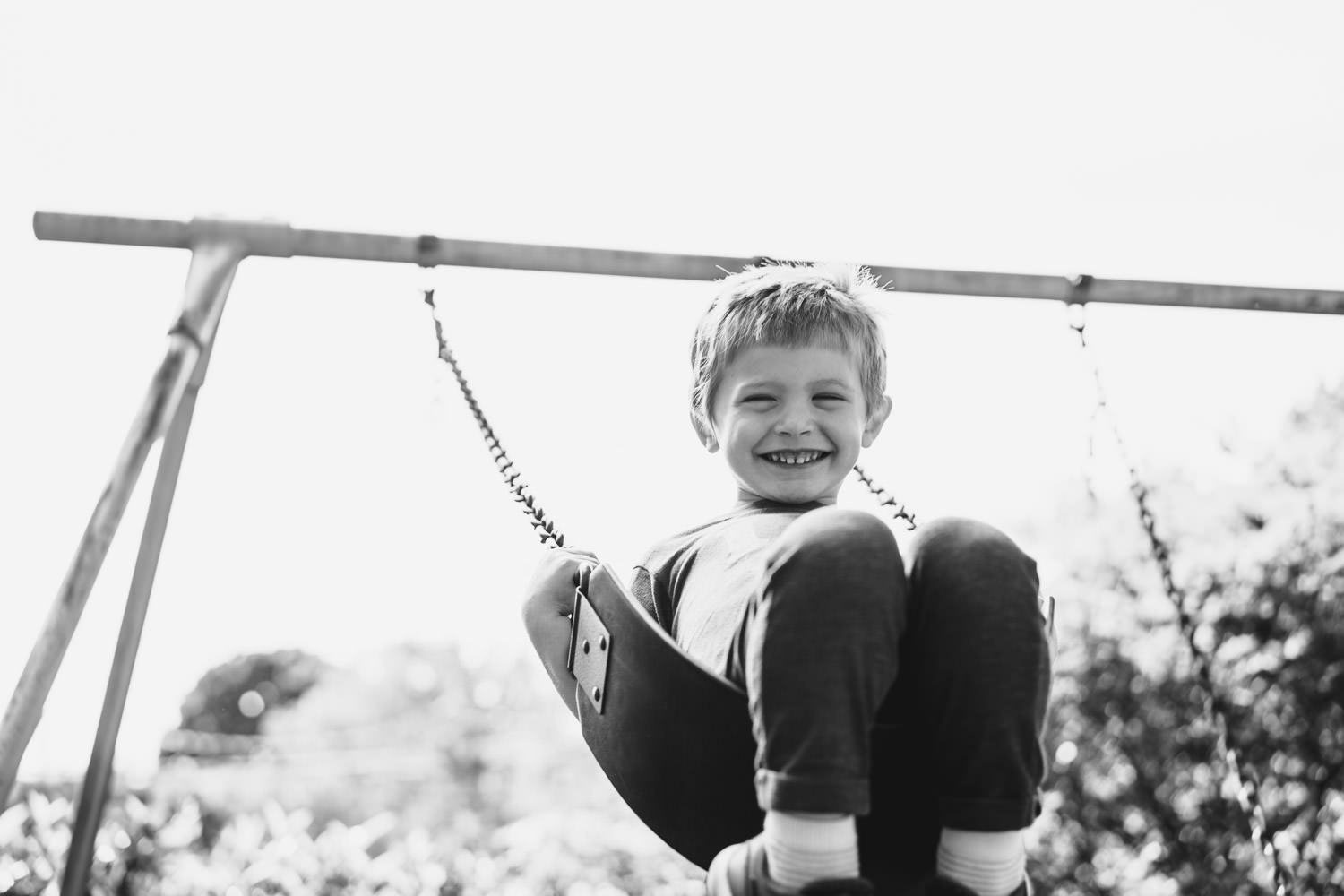 A little boy swings on a swing.