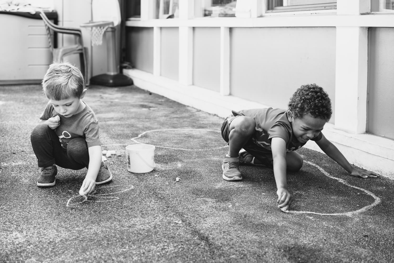 Two boys draw on the cement with chalk.