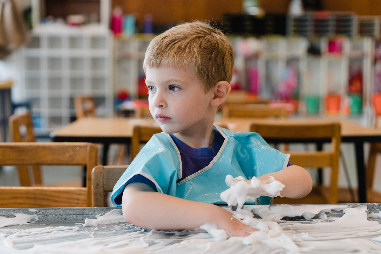A little boy plays with shaving cream at preschool.