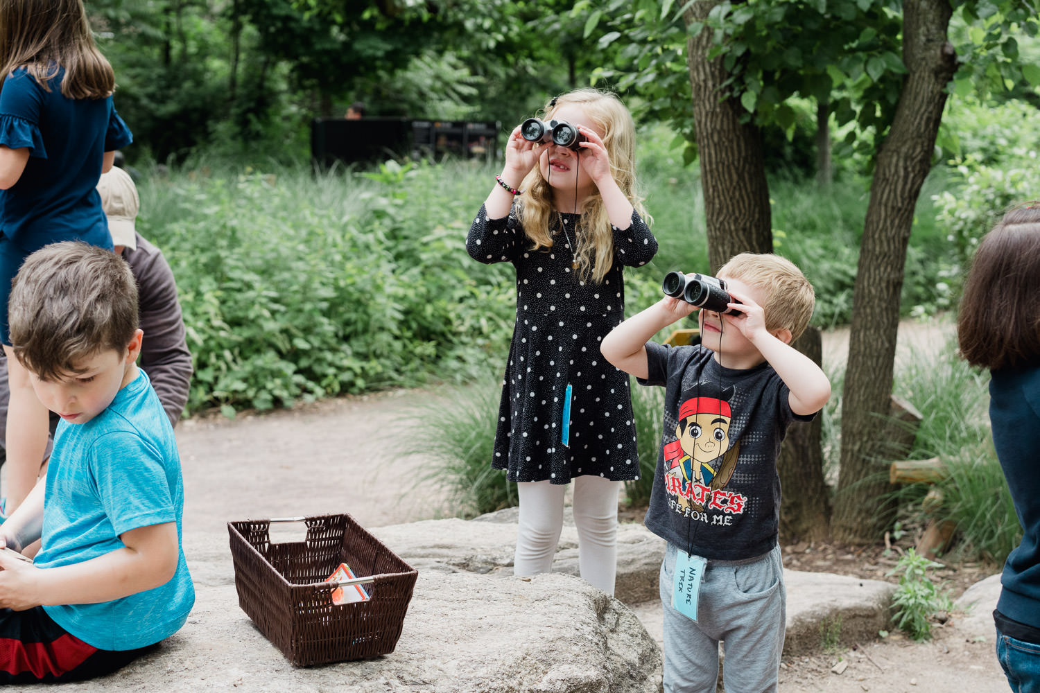 Two young kids look through binoculars at the Nature Trek at the Bronx Zoo.