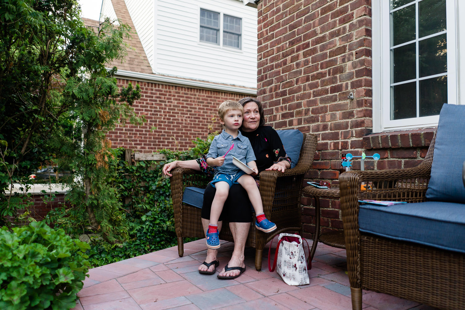 A little boy sits on his grandmother's lap on a front porch.