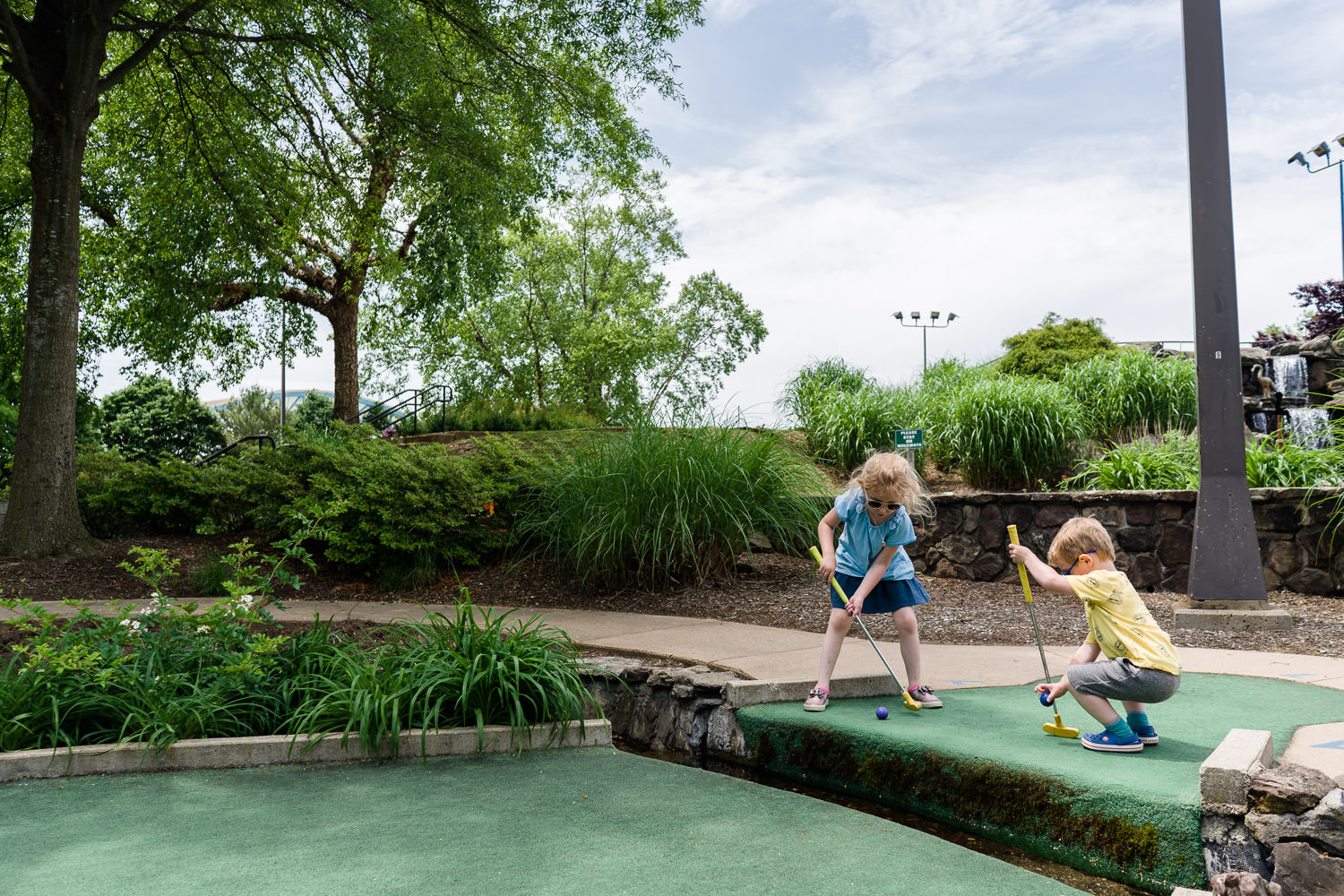 Two children play mini golf.