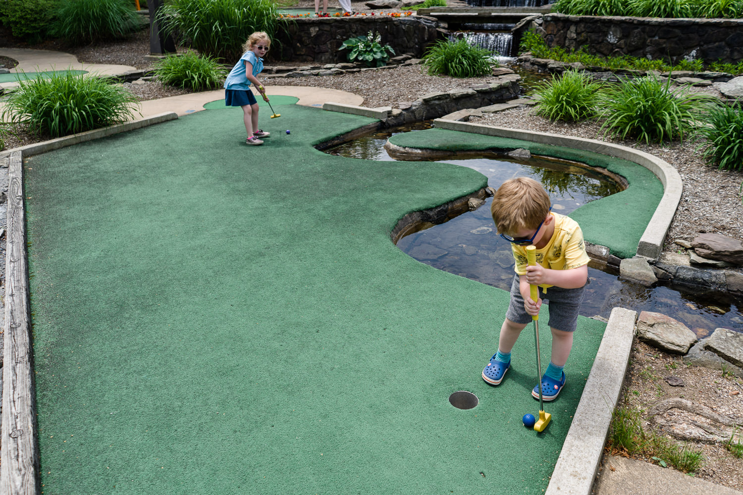 Two children play mini golf at Eisenhower Park.
