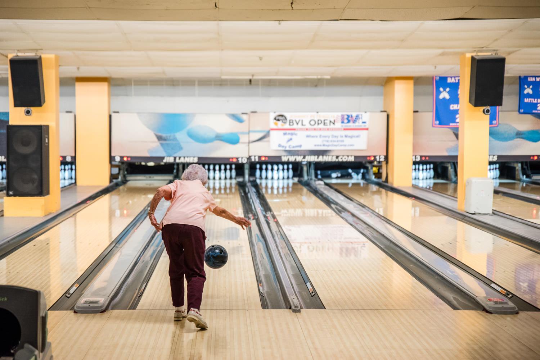 An elderly woman bowls.