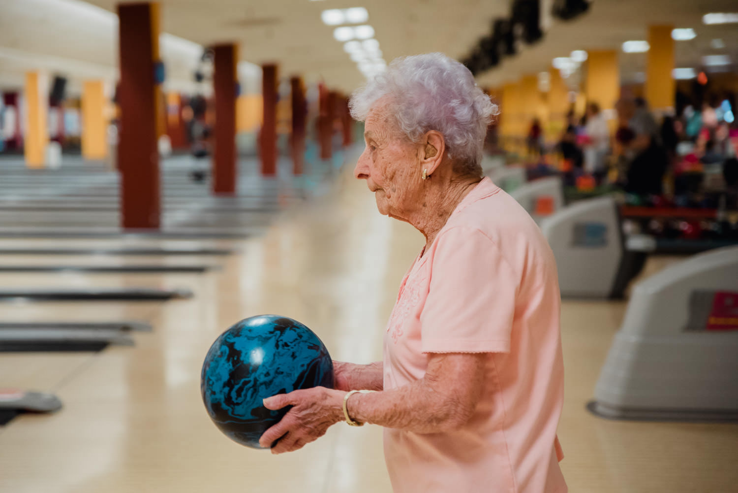 A 100 year old woman bowls.