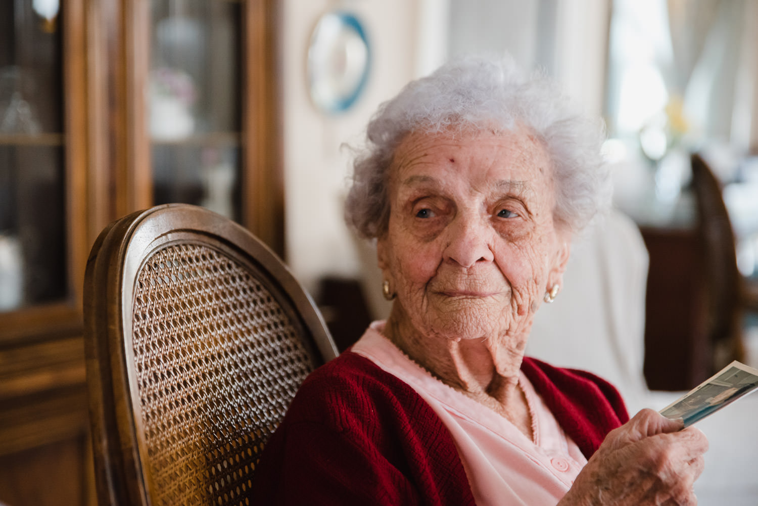 A 100 year old woman seated in her home.