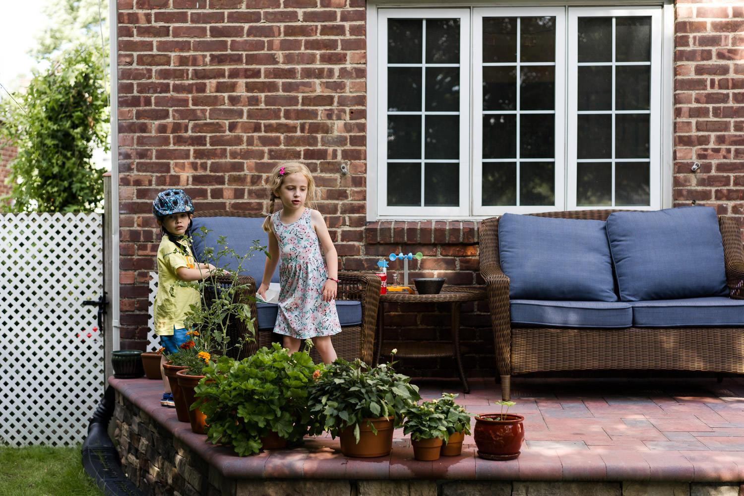 Two children play on a porch.
