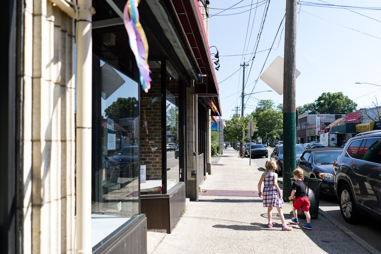 Two children walk down a street.