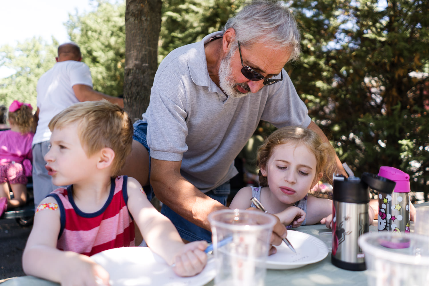 A grandfather helps his grandkids with word games.