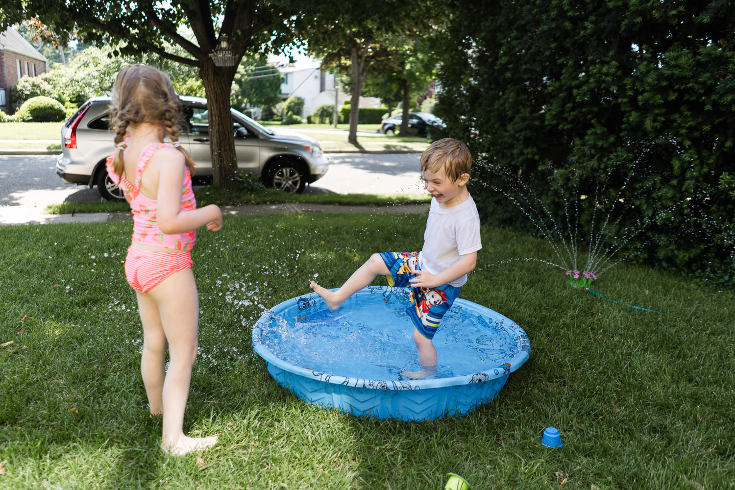 Two kids play with a kiddie pool on a lawn.