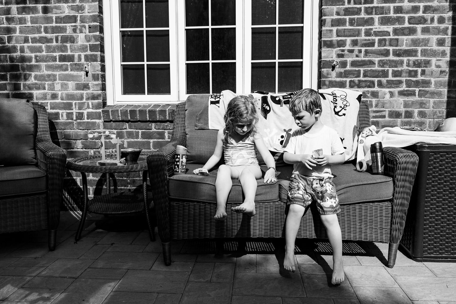 Two kids in swimsuits sit on a porch.