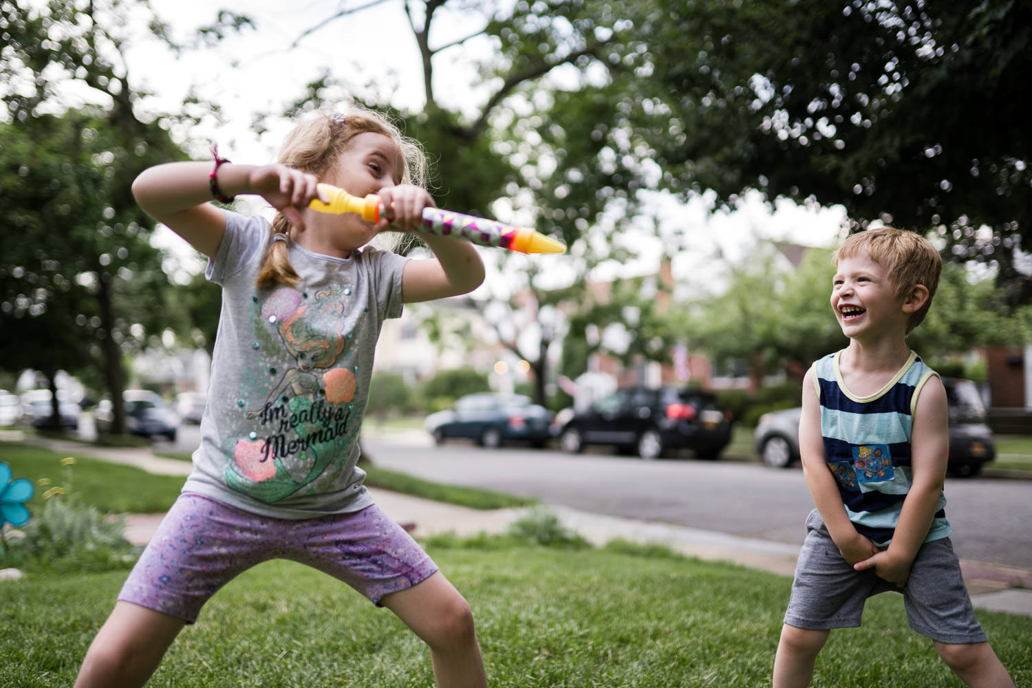 A little boy and girl play with a water gun.
