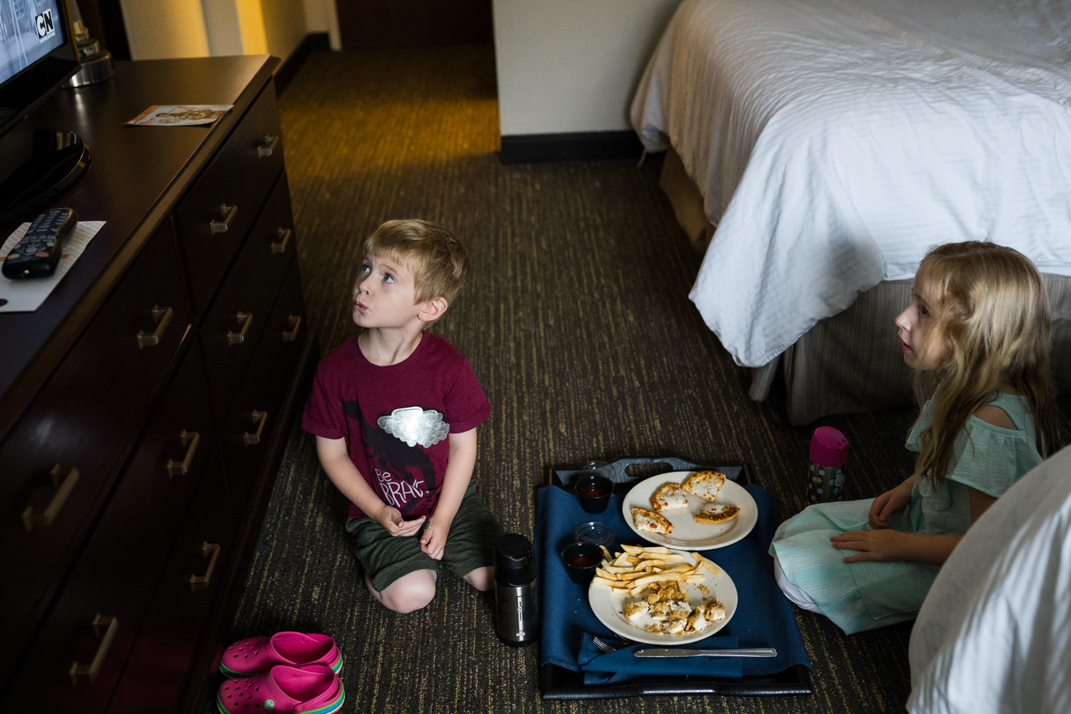 A little boy and girl eat room service dinner on the floor of a hotel room.