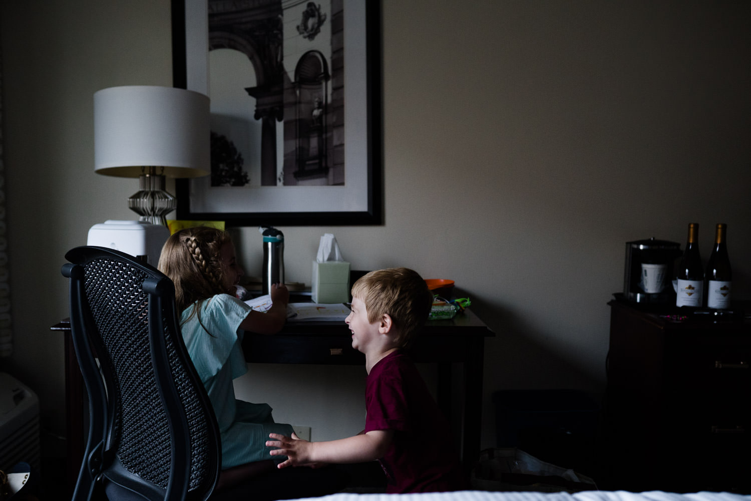 A little boy laughs at his sister by a hotel room desk.