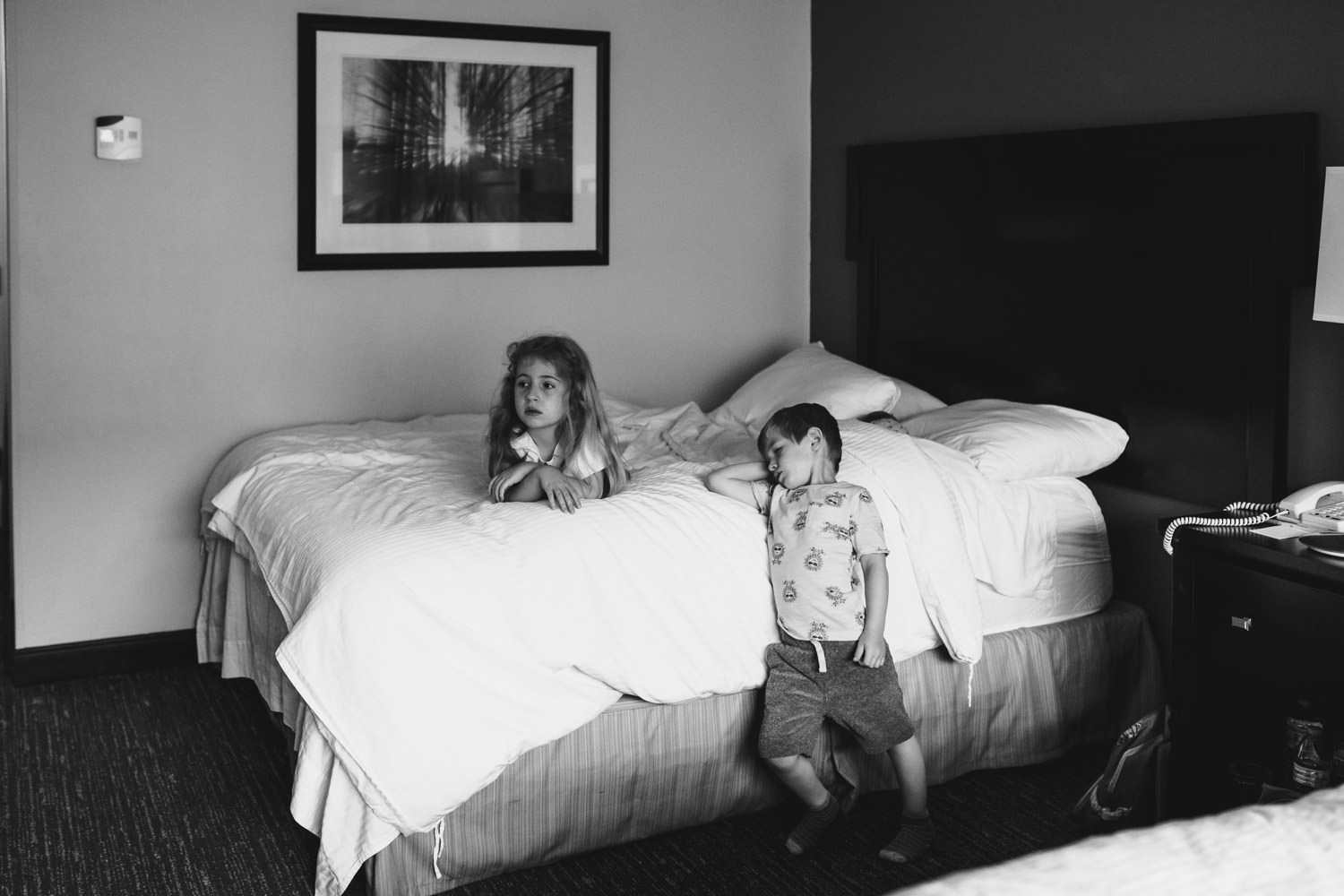 Children watch tv from a hotel room bed.