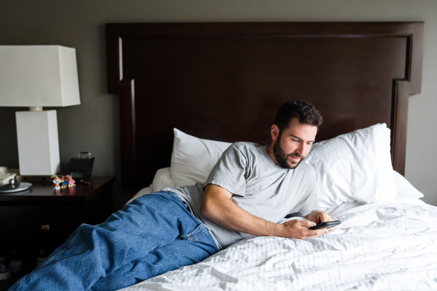 A man checks his cell phone in a hotel room.