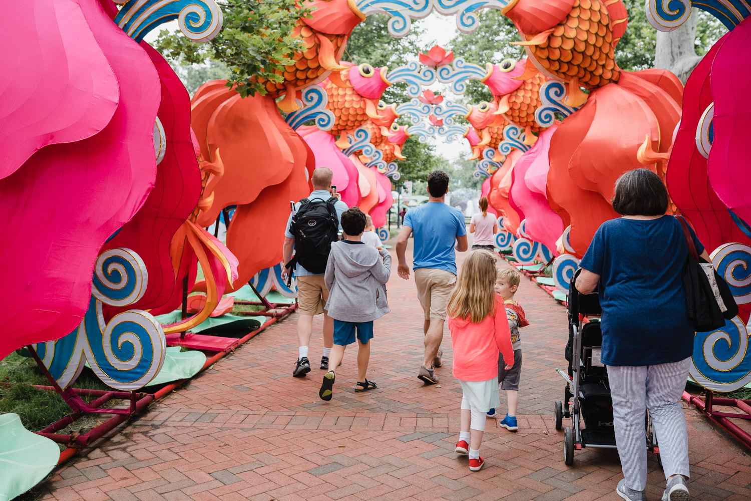 Family members walk through chinese lanterns in a Philadelphia park.