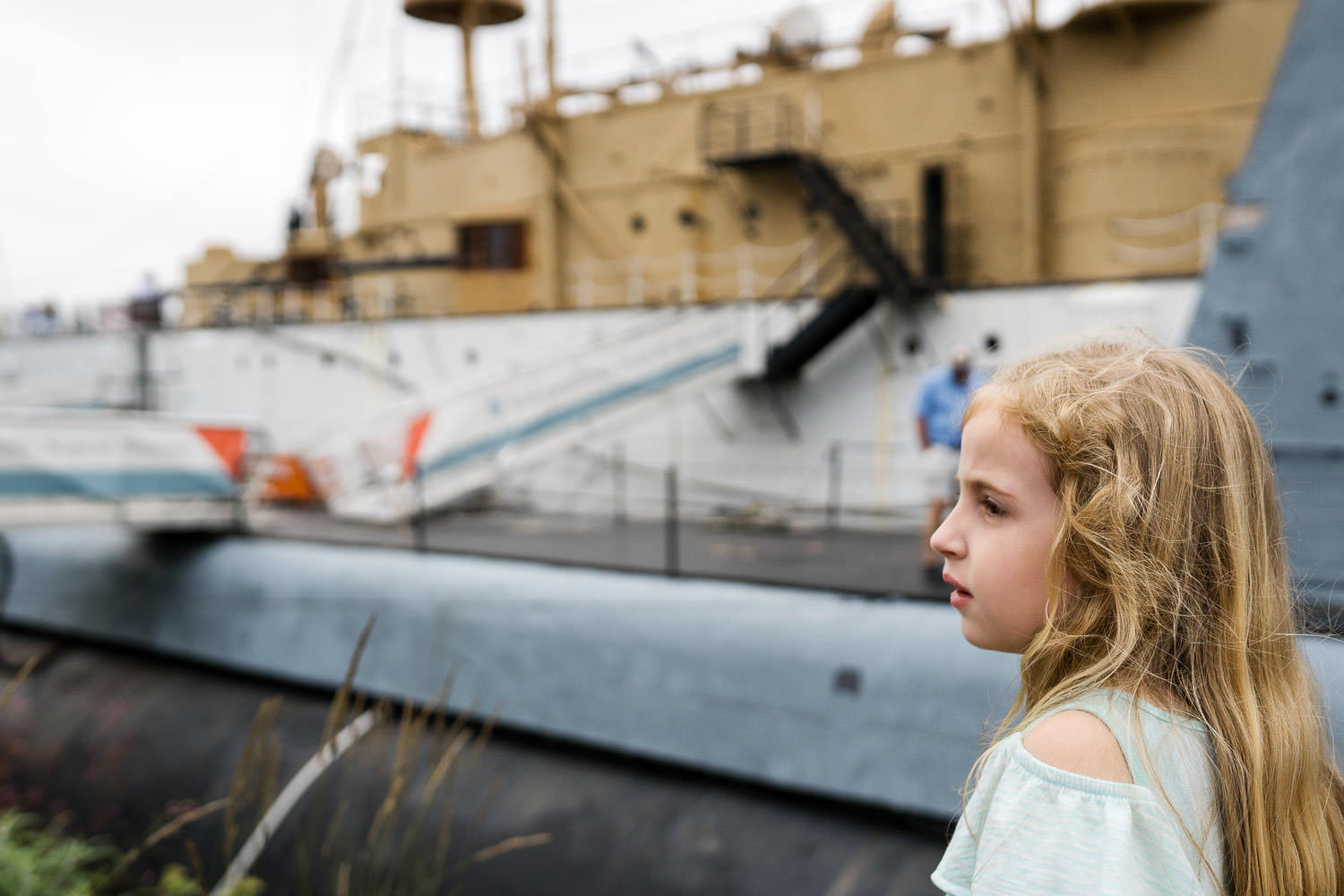 A little girl looks out from a pier at a large boat.