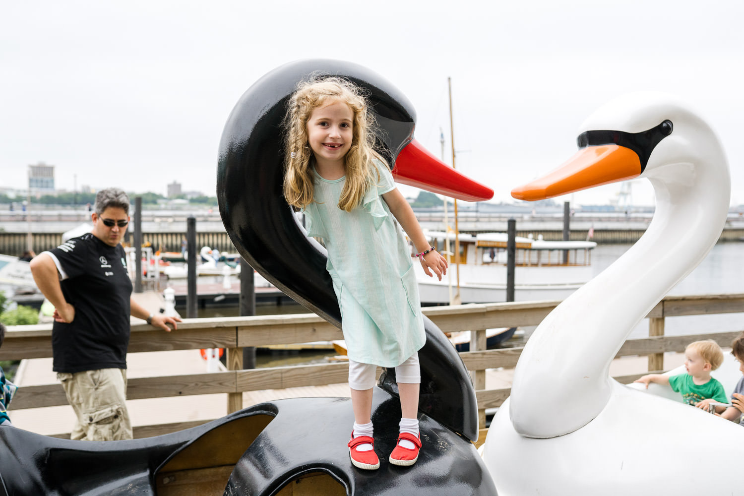 A little girl stands on some swan boats on a pier.