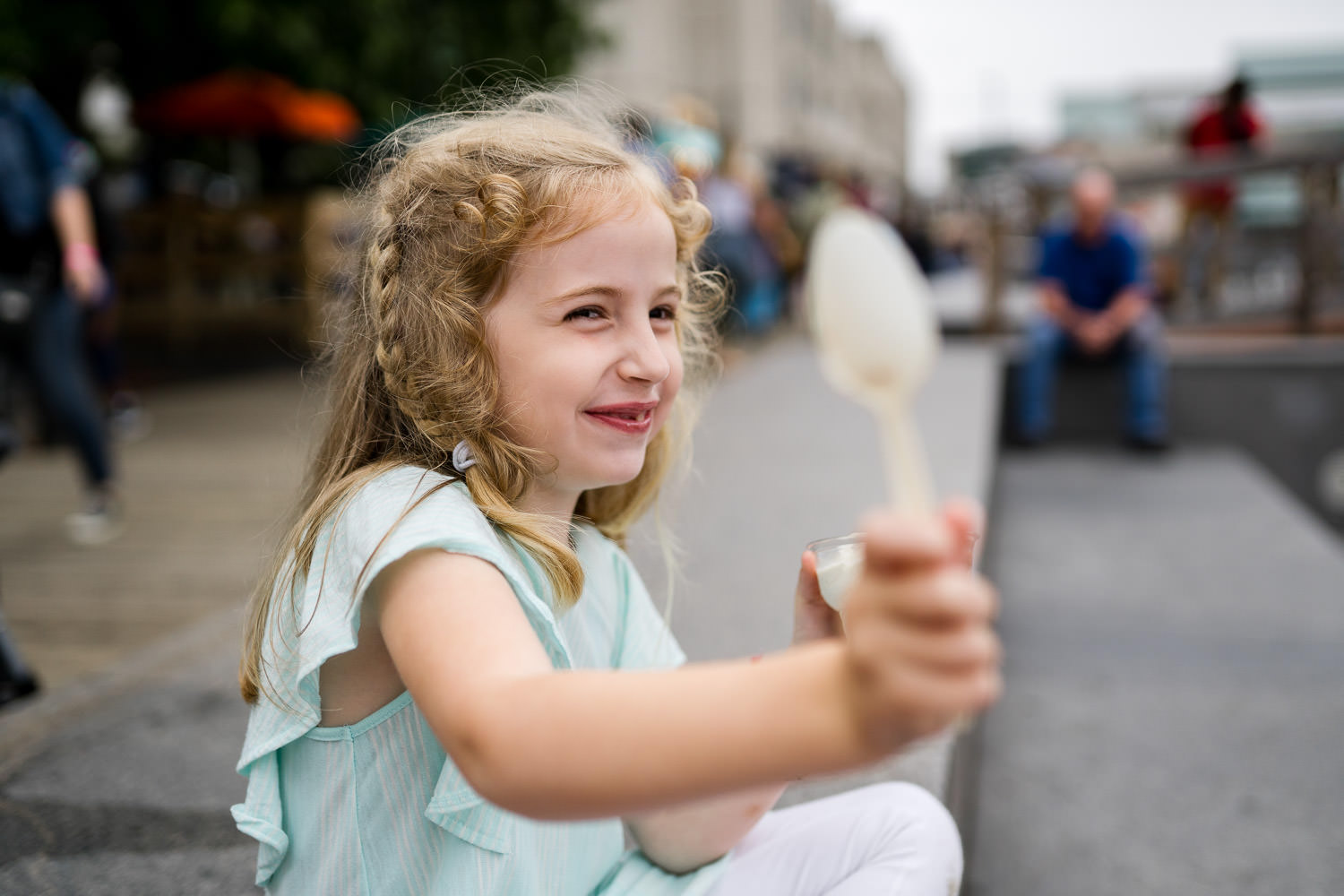 A little girl smiles while eating ice cream.