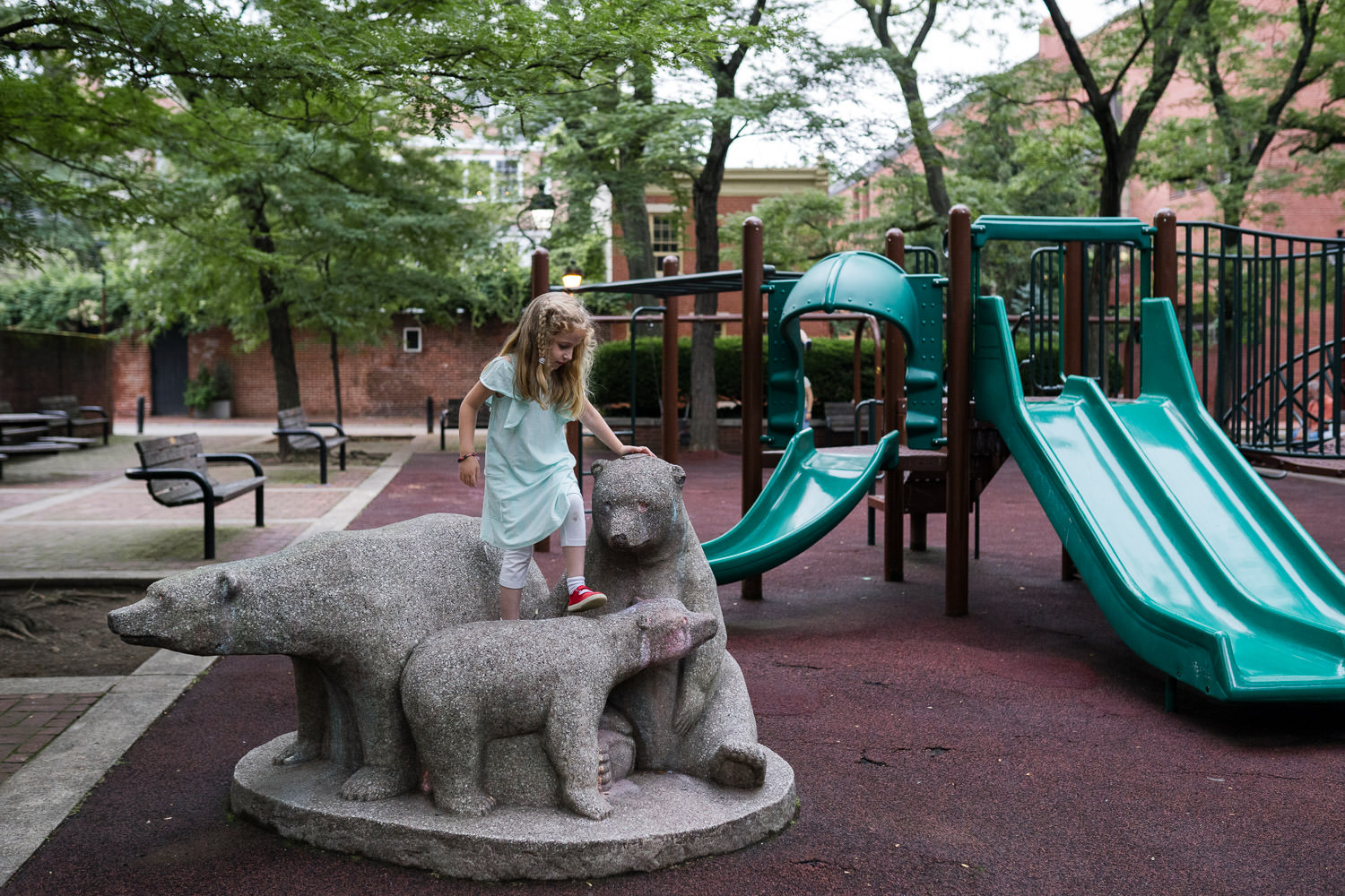 A little girl climbs a statue of three bears at a playground.