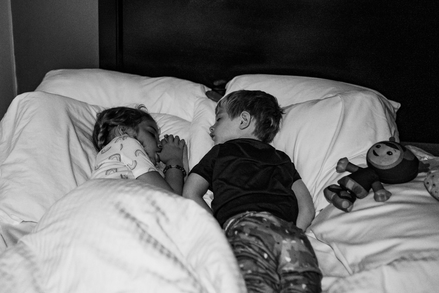 Two children asleep in a hotel bed.