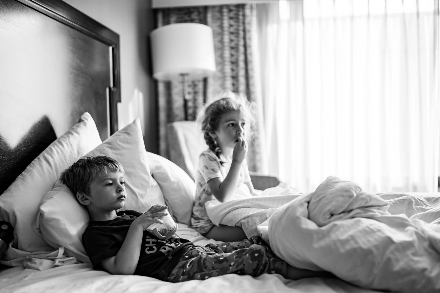 Two kids watch tv and eat breakfast in a hotel bed.
