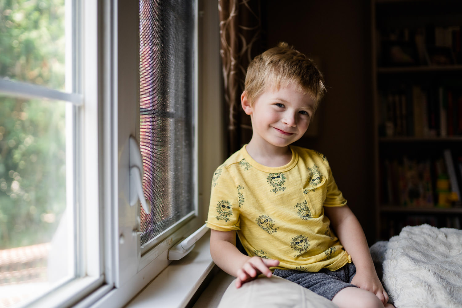 A little boy smiles next to a window.