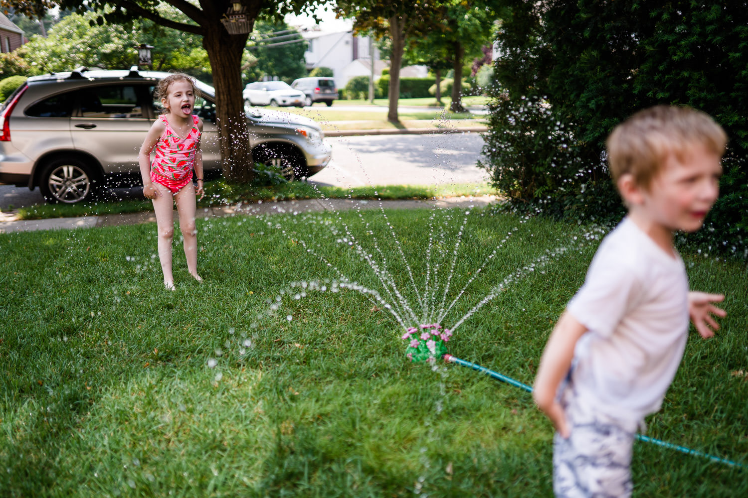 Children play in a sprinkler on the grass.