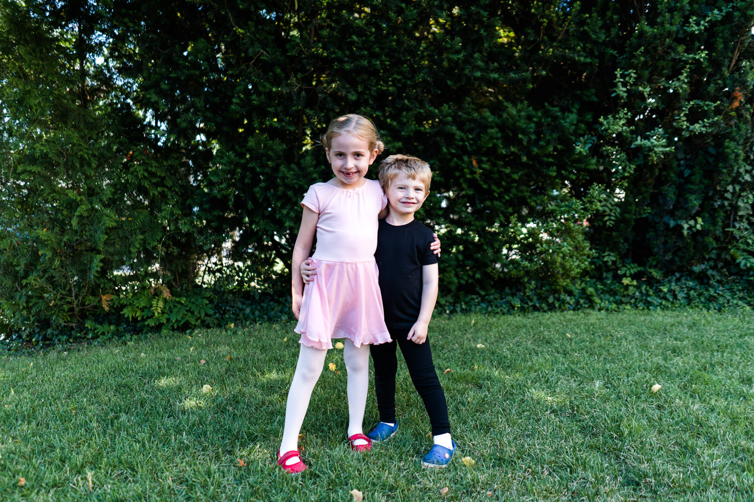 Two children in dance clothes stand on a lawn.