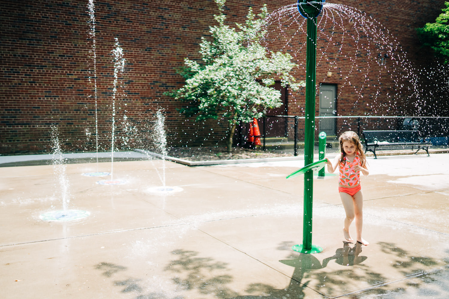 A little girl plays in a sprinkler at the park.