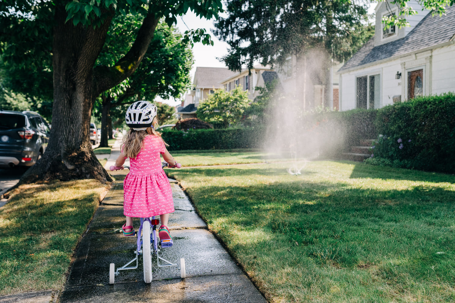 A little girl rides her bike by a sprinkler.