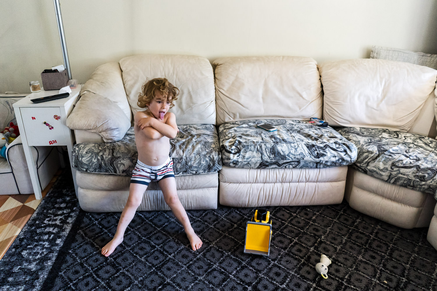 A little boy stands in his living room in his underwear.