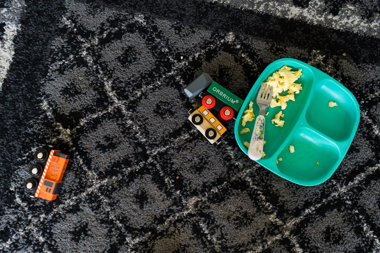 Some toys and a toddler plate of scrambled eggs.