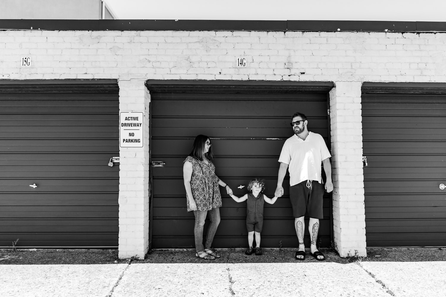 A family holds hands in front of a garage.