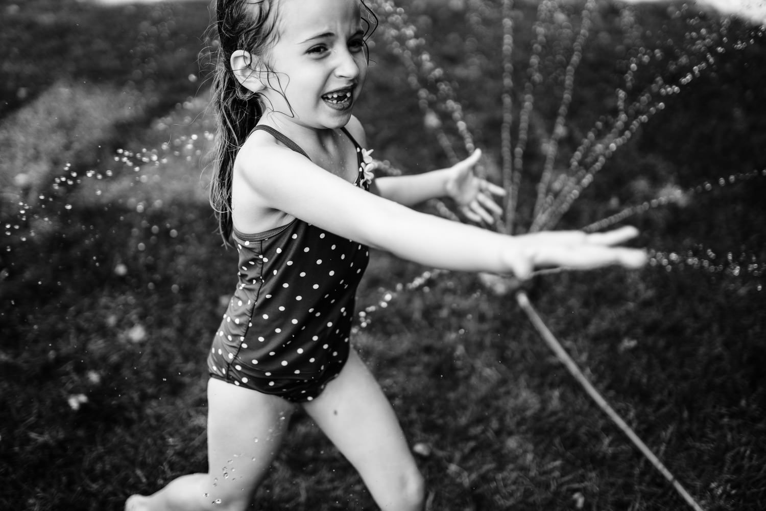 A little girl plays in the sprinkler.