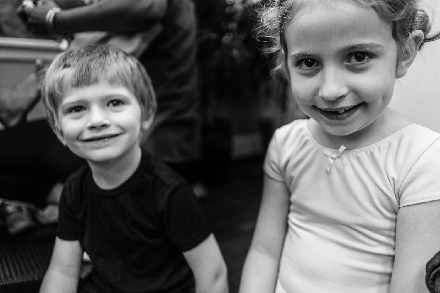 A little boy and girl smile at the camera before their dance class.