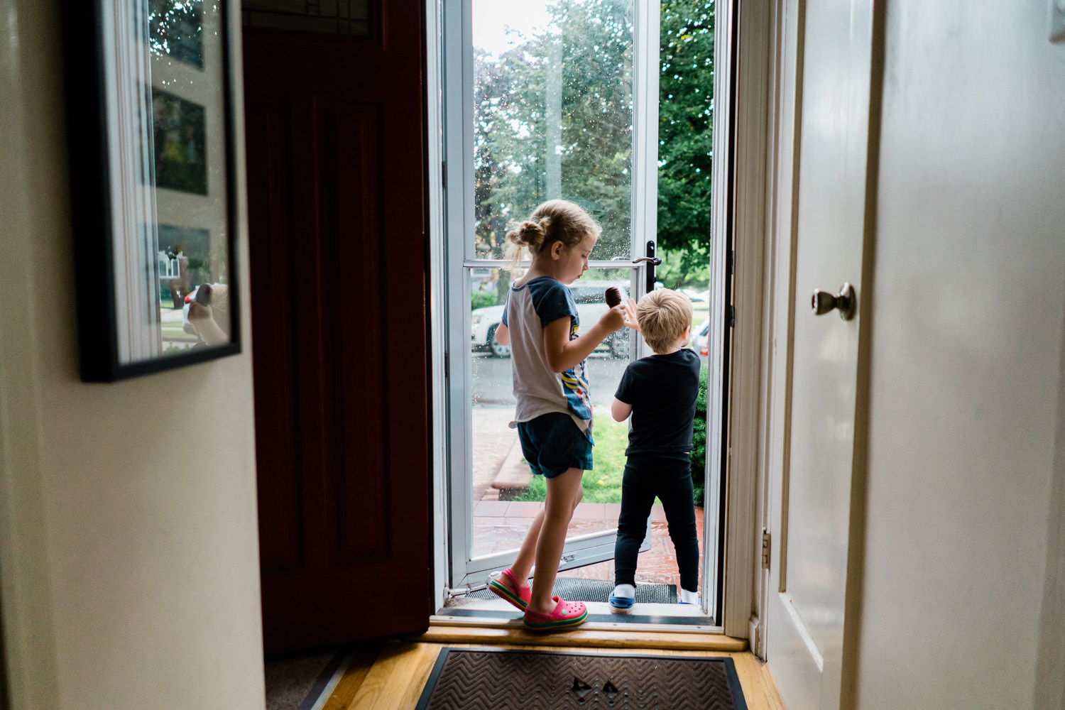 A little boy and girl slip outside their front door.