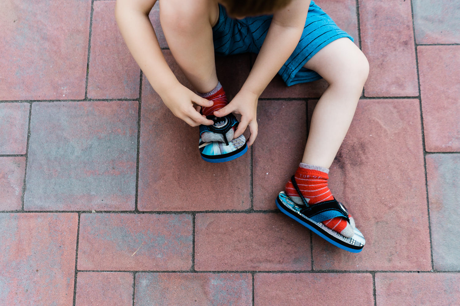 A little boy tries to put flip flops on with socks.