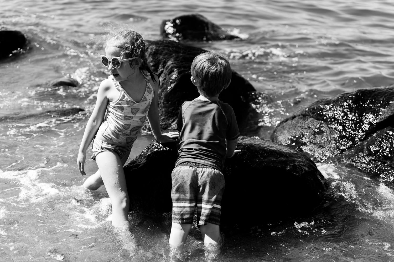 A boy and girl play in the water at Sands Point.