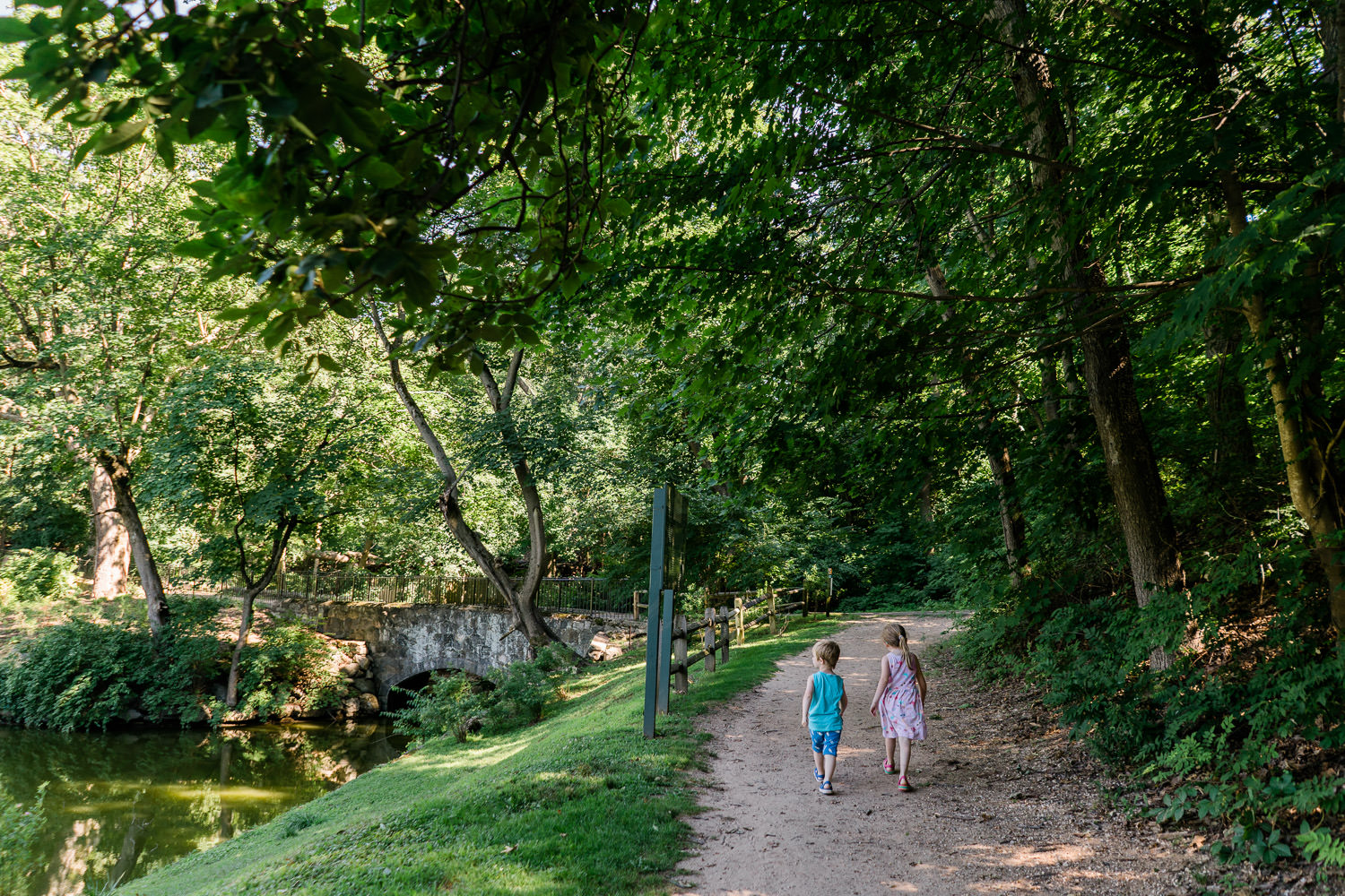A boy and girl walk down a trail together.