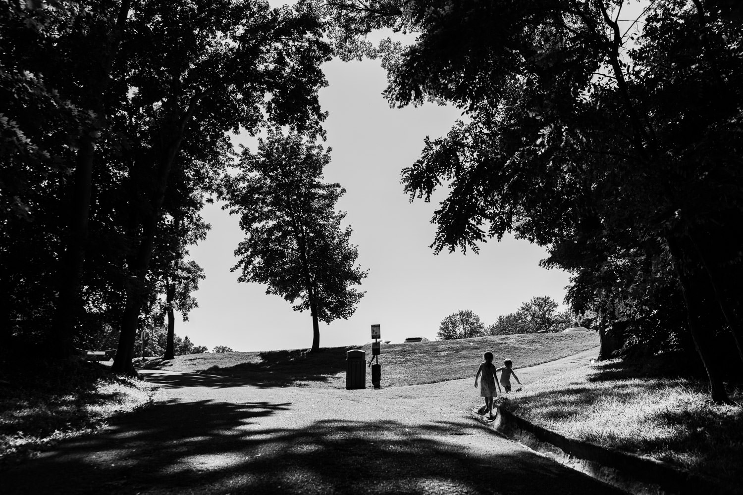 A silhouette of a boy and girl walking along a trail.