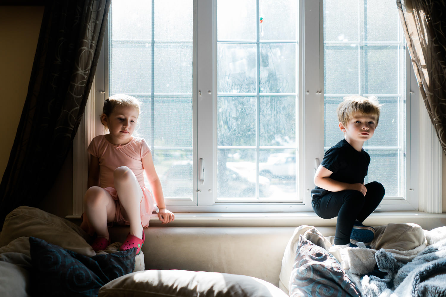 Two children dressed in dancewear perch on the back of a couch.