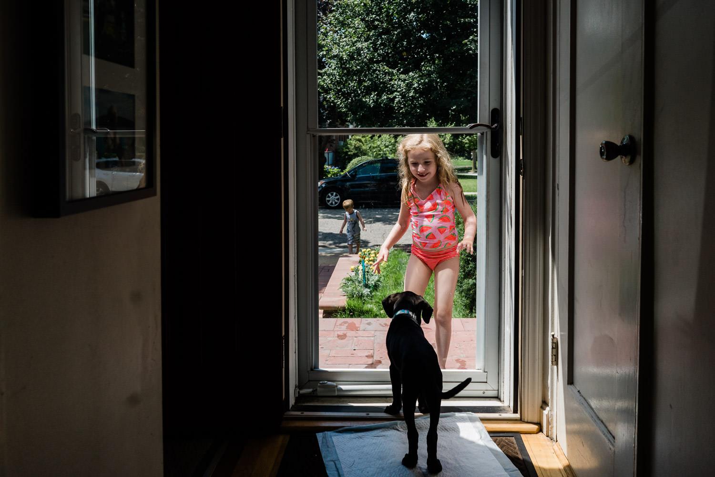 A little girl looks at her puppy through a screen door.