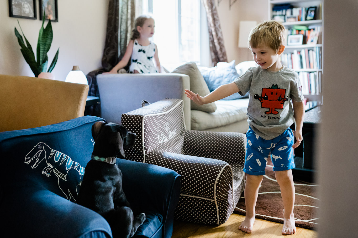 A little boy tells his dog to stop.